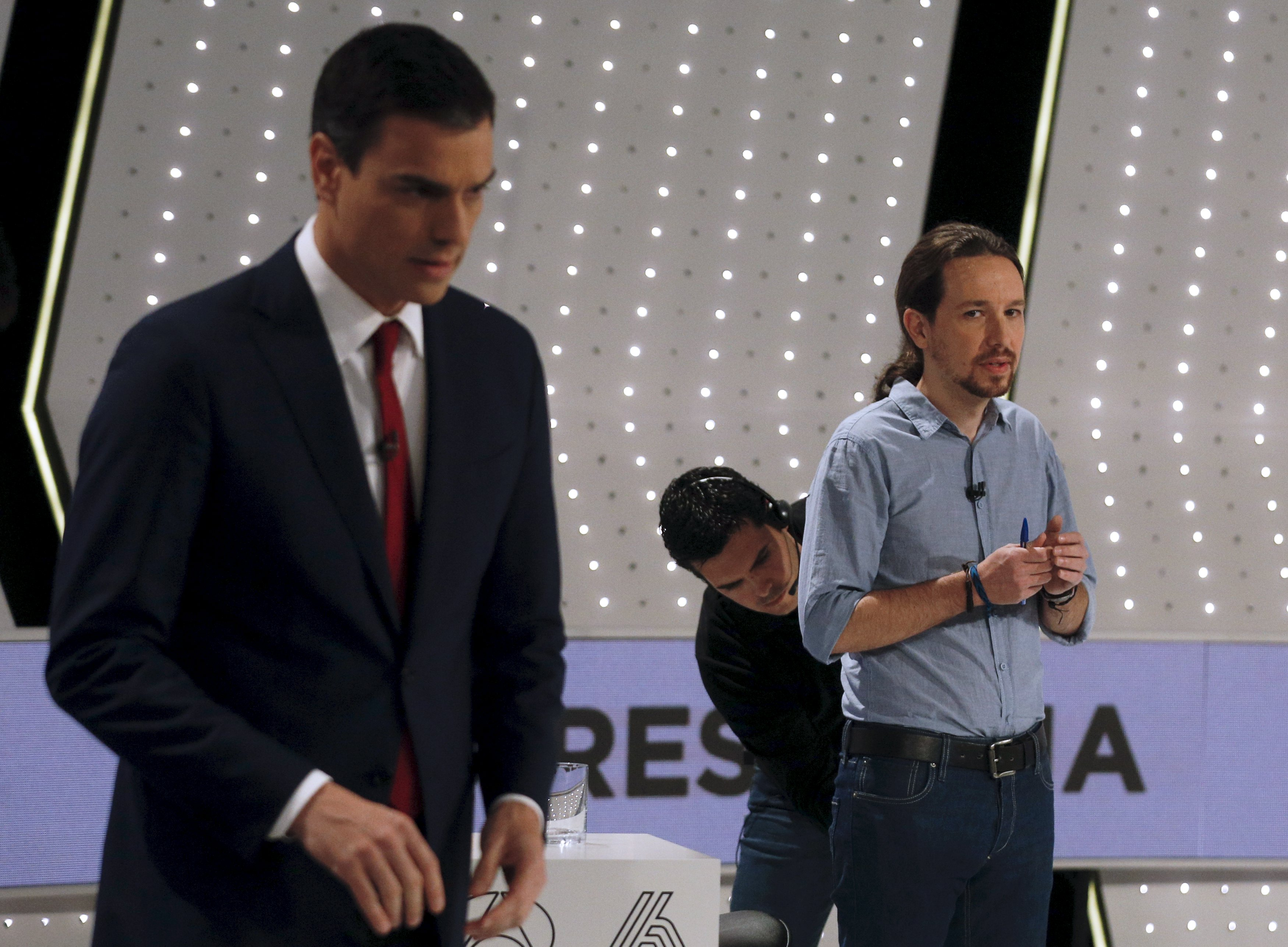 Podemos (We Can) party leader Pablo Iglesias (R) has his microphone adjusted by a technician as Socialist party (PSOE) leader Pedro Sanchez stands before a live debate hosted by Spanish media group Atresmedia in San Sebastian de los Reyes, near Madrid, Spain, December 7, 2015. REUTERS/Sergio Perez